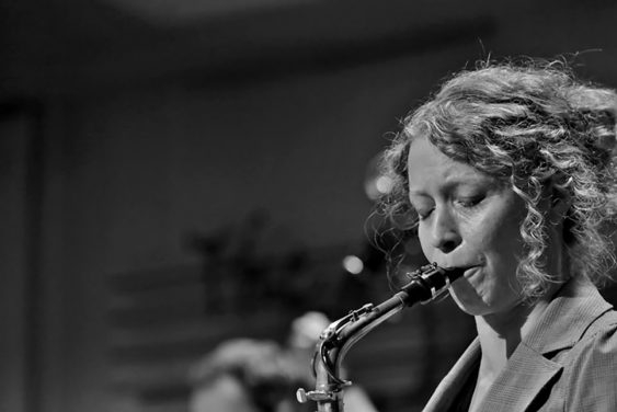 A black and white photo of Kasey Knudsen playing the saxophone.
