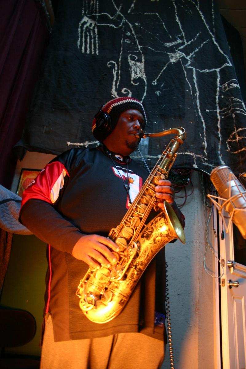 Kamazi Washington playing an underlit saxophone.