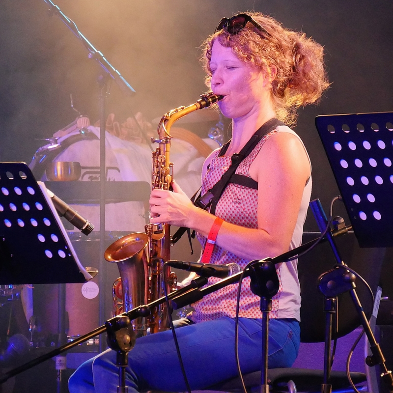 A photo of Kasey Knudsen playing the saxophone while live on stage.
