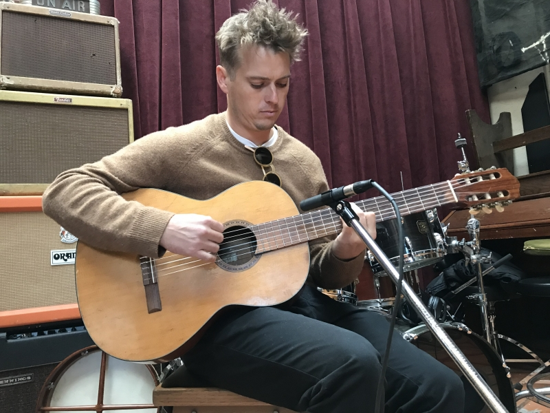 A photo of Ross Howe playing guitar at Wide Hive Records in Berkeley, California.