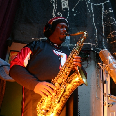 Kamazi Washington playing an underlit saxophone.