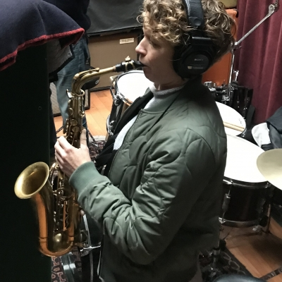A photo of Kasey Knudsen playing the saxophone at Wide Hive Records in Berkeley, California.
