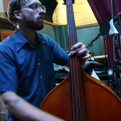 "Matt Montgomery Playing the standup base on the album ""Heavy Feel."""