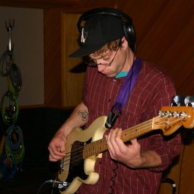 "Matt Montgomery playing bass on the album ""Throttle Elevator Music."""