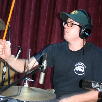 "Mike ""Lumpy"" Hughes, playing drums on the album ""Throttle Elevator Music,"" on Wide Hive Records."