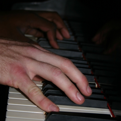 A photo of the Wide Hive Players at the piano.